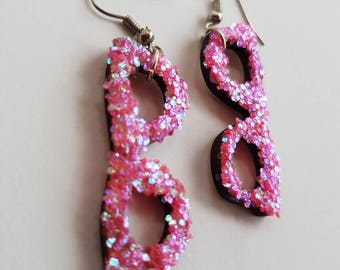 Sparkly pink nerdy geek glasses earrings made from wood and covered in glitter.