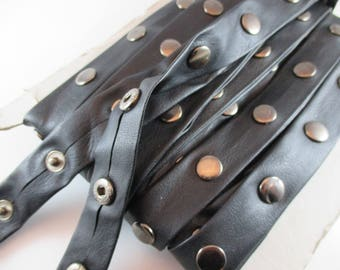 Band of metal snap buttons, black faux leather, width 2.5 cm.