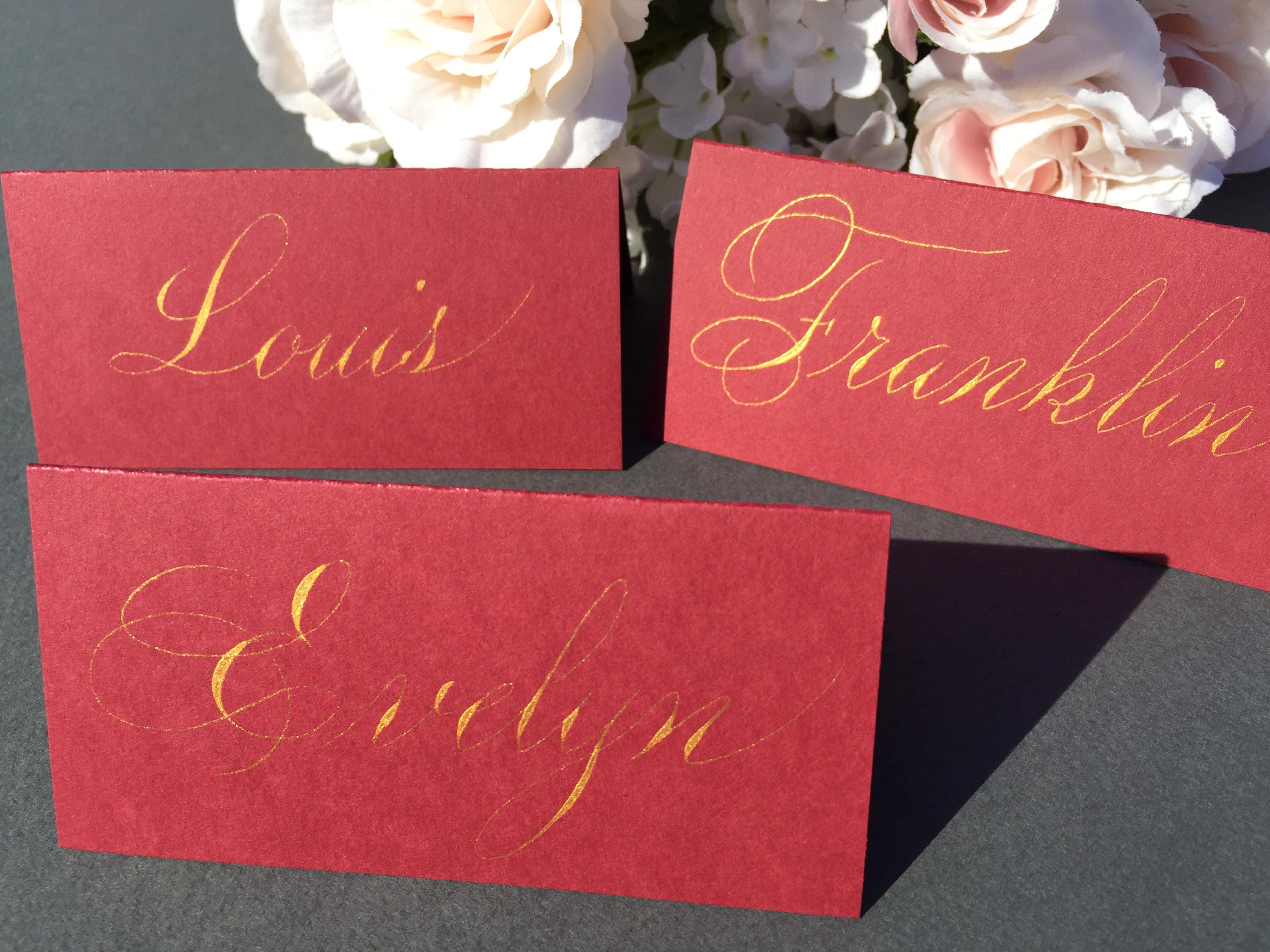 custom gold writing place cards in red for weddings dinners