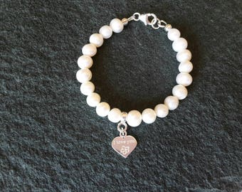 Sterling silver 925 flower girl/bridesmaid bracelet made with white fresh water pearls, sterling silver heart charm saying I love you.