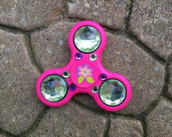 One of a kind pink fidget spinner with blue rhinestones and flower embellishments.