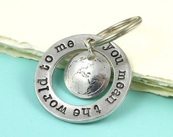 Ring Charm Keyring with a world map In Pewter with the message You mean the world to me stamped around it.