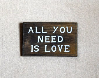 Wooden table with an inscription hand painted: ALL you NEED is LOVE