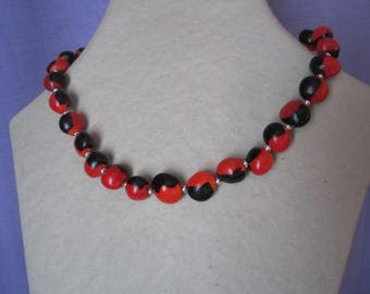 Necklace with seeds of caconnier red and black with silver beads.