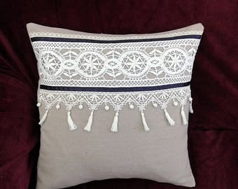 Pillow adorned with grey linen with a bobbin of embroidery