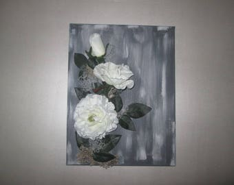 Table with artificial white rose flowers on gray background