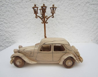 Under the fire of lights. Wooden miniature of a Citroen traction before 11 CV car.