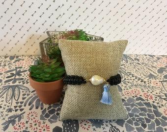 Black bracelet with blue tassel and pearl
