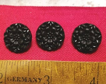 Three black plastic sewing buttons with floral pattern