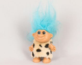Troll Doll Leopard skin removeable dress Rounded ears Soft vinyl body Turquoise blue hair Bright blue eyes black pupils 4 inches tall