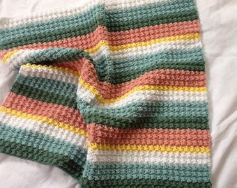 Brightly coloured green and peach stripy crochet baby blanket, thick snuggly pram blanket for babies and toddlers