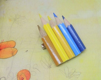 Large brooch with yellow, blue and blue colored pencils