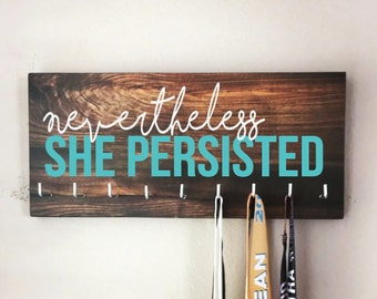 "Race Medal Holder - ""Nevertheless, SHE PERSISTED"" white and teal with wood grain background - Elizabeth Warren"
