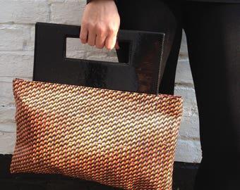 Unique raffia hand bag with rigid black patent handles.