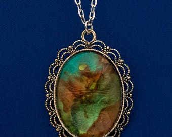Hand painted Oval Filagree Pendant necklace with shades of turquoise and brown.