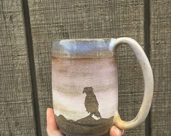 Rustic handmade ceramic mountain mug with hawk flying over soft pink sunset