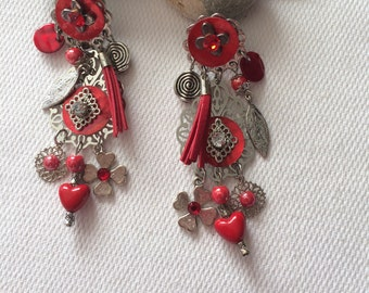 pierced earrings with carved print surrounded by beads of Red rhinestones and charms