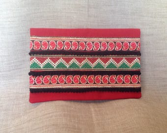 Pocket flap with red fabric, ribbons and tassels.