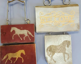 Two double wooden horse signs with bit hangers.