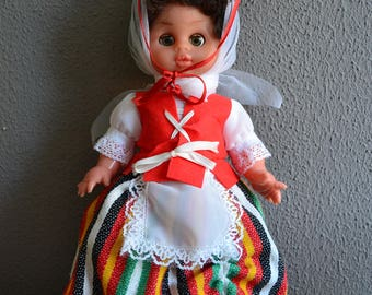 Cute vintage European souvenir doll in traditional dress with hat