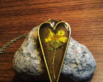 Heart pendant with small yellow wild flower
