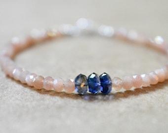 peach moonstone bracelet with 'big' iolite detail. iolite gemstone and moonstone bracelet. violet and peach moonstone beaded bracelet