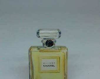 A classic Chanel Allure perfume bottle acrylic brooch pin