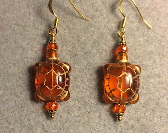 Translucent orange Czech glass turtle bead earrings adorned with orange Chinese crystal beads.