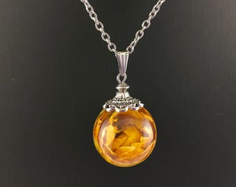Resin pendant bubble and yellow Rosebud dried fine stainless steel necklace.