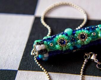 Collier court argenté, pendentif cylindre en perles tons bleus