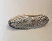 For ann Art Deco 14k white gold Oval Shaped Filigree Pin with a Seed Pearl Center by Krementz