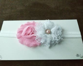Newborn headband with pink and white flowers on a white band.