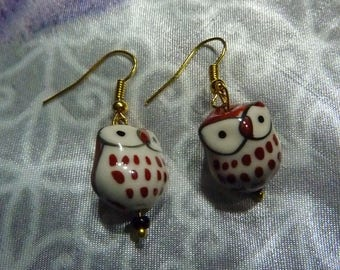 Golden metal earrings with a brown owl made with ceramic and beads