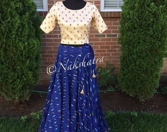 Blue ikkath lehenga paired with a designer top. Prestitched and ready to be adjusted to your size.