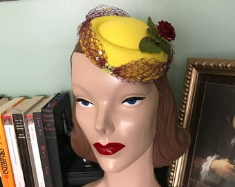 Yellow pillbox hat with burgundy rose