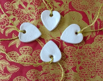 Four heart-shaped clay white favours/tags