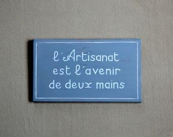 Tableau en bois patiné avec l'inscription : L'Artisanat est l'avenir de deux mains - Création Originale