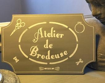 "Painted gray and white ""Atelier de embroiderer"" wooden door plaque"