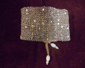 Bracelet tissé en pièce unique, fait de perles écrues.