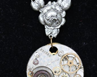 Vintage victorian steampunk recycled upcycled and clock parts costume jewlery pendant necklace with exposed gears in gold and silver tones.