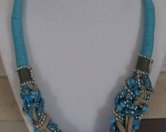 Turquoise and silver necklace, beads and fabric.