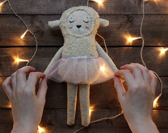 Cute toy for baby. Sleeping sheep doll lamb in a skirt
