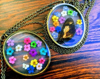 Rainbow Daisies - Tiny Rainbow Daisies w/ Butterfly (naturally passed) Preserved in Resin enclosed in Large Oval Bronze Pendant Necklace