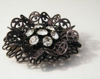 Filigree Black Flower Brooch with Rhinestone accent, vintage lace look round pin, 7 rhinestones in center bloom, mid century costume jewelry