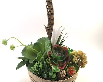 Faux succulent plant arrangement in round wicker straw basket with bird feathers and wicker sphere