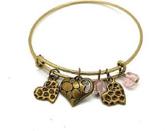 Fancy bracelet type bronze ring and hearts and pink spun beads charms and key charms