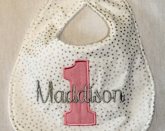 Girl's First Birthday Bib  - Pink 1 on Silver metallic dot fabric with name embroidered in Silver Metallic thread.