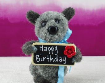 Small grey bear/dog holding Happy birthday sign.