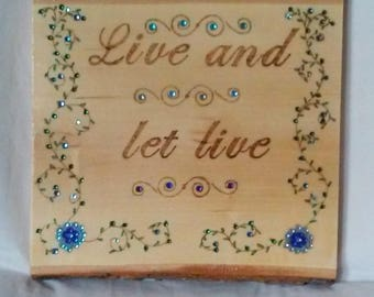 Wood burned plaque with the quote Live and let live, decorated with flowers and vines, painted and embellished with colored crystals