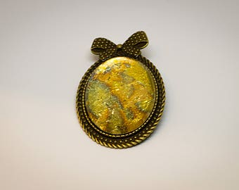 Cabochon brooch, gold color, glitter. With sheet metal deposited.